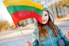 Cute little girl celebrating Lithuanian Independence Day holding tricolor Lithuanian flags. In Vilnius Stock Photos