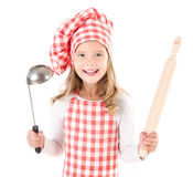 Cute little girl in chef hat with ladle and  rolling pin. Smiling cute little girl in chef hat with ladle and  rolling pin isolated on a white Stock Photography