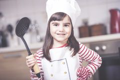 Little girl chef. Cute little girl chef posing in the kitchen Royalty Free Stock Photography