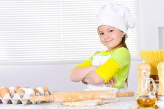 Cute little girl in chef`s hat baking cake in the kitchen. At home Stock Photography