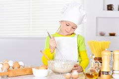 Cute little girl in chef`s hat baking cake in the kitchen. At home Royalty Free Stock Image