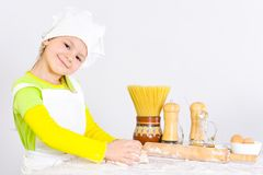 Cute little girl in chef`s hat baking cake in the kitchen. At home Stock Image