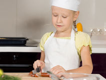 Cute little girl in a chefs uniform cutting food Royalty Free Stock Images