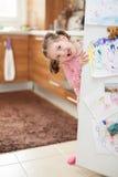 Cute little girl chewing gum behind refrigerator door in kitchen stock images
