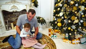 Cute Daddy Daughter And Dad Playing on Tablet Sitting on Floor in Bright Room on Background of Festively Decorated. Cute Little Girl Child Holding Gadget and stock footage