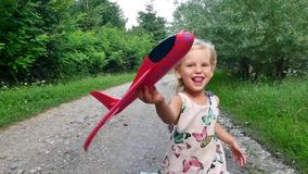 Cute little girl child playing with airplane toy in park at sunset golden hour childhood innocence play concept slow. Motion shot stock video