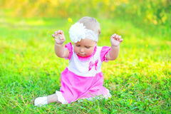 Cute little girl child with yellow flower sitting on grass Royalty Free Stock Photography