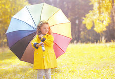 Cute little girl child in yellow jacket with colorful umbrella Stock Photos