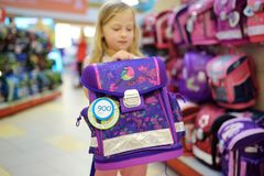 Cute little girl choosing a schoolbag before starting classes. Adorable pupil buying school backpack in a store. Back to school concept stock photography
