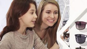 Cute little girl choosing sunglasses with her older sister at the store stock footage