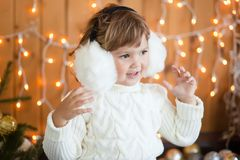 Cute little girl and christmas decor, beautiful light. Royalty Free Stock Image