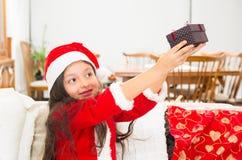 Cute little girl in Christmas dress holding Stock Photos