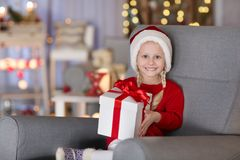 Cute little girl with Christmas gift box sitting in armchair. At home Royalty Free Stock Photos