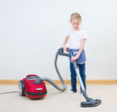 Cute little girl cleaning carpet. Stock Photo