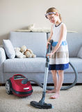 Cute little girl cleaning carpet. Royalty Free Stock Photo
