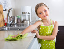 Cute little girl cleaning at kitchen. Cheerful cute little girl dusting table with rag at home kitchen Stock Photos