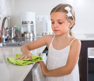 Cute little girl cleaning at kitchen. Cute little girl cleaning table at home kitchen royalty free stock photo