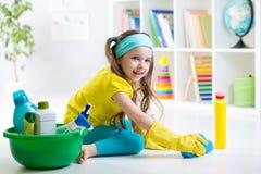 Cute little girl cleanses a floor. Cute kid little girl cleanses a floor in children room stock photo