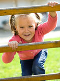 Cute little girl is climbing up on ladder royalty free stock photos