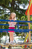 Cute little girl is climbing up on ladder in playground Royalty Free Stock Images