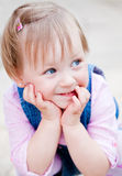 Cute Little Girl. Close-up portrait of a cute little girl with blue eyes holding her face in her arms Royalty Free Stock Photography