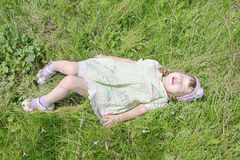 Cute little girl with closed eyes lies on grass Royalty Free Stock Photos