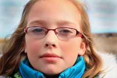 Cute Little Girl. A closeup of a cute little somber blond 9 year old girl wearing glasses and a warm blue winter hoody coat.  Shallow depth of field Stock Photography