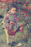 Cute little girl collects wild berries in the woods Stock Image