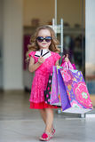 Cute little girl with colorful bags for shopping in supermarket Stock Images