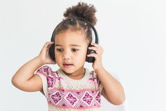 Cute little girl in a colorful dress listening to music with headphones on a white background royalty free stock photography