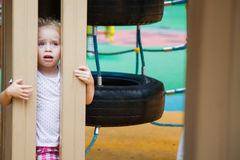 Cute little girl on a colorful playground Stock Photos
