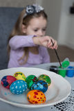 A cute little girl coloring easter eggs Royalty Free Stock Photos