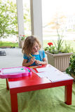 Cute little girl coloring in on an outdoor patio Royalty Free Stock Photography