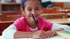 Cute little girl colouring in book in classroom smiling at camera. In elementary school stock footage