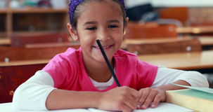 Cute little girl colouring in book in classroom smiling at camera. In elementary school stock video