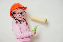 Cute and little girl in a construction helmet hard hat and glasses holding paint roller paints a white wall at home