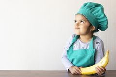 Cute little girl cook playing with a banana stock images
