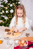 Cute little girl cooking Christmas cookies in kitchen stock image