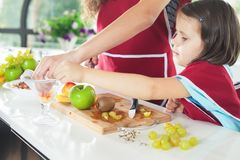 Cute little girl cooking with her mother. Healthy food, fruits Royalty Free Stock Photos