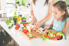 Cute little girl cooking with her mother, healthy food Royalty Free Stock Photo