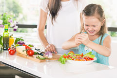 Cute little girl cooking with her mother, healthy food. Cute little girl cooking with her mother. Healthy food, cooking healthy salad with vegetables ingredients Royalty Free Stock Image