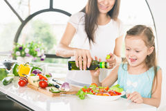 Cute little girl cooking with her mother, healthy food Royalty Free Stock Photography
