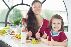 Cute little girl cooking with her mother, healthy food. Yogurt Stock Photography