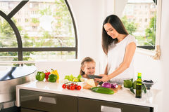 Cute little girl cooking with her mother at kitchen Royalty Free Stock Photos