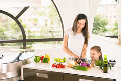 Cute little girl cooking with her mother at kitchen Royalty Free Stock Images