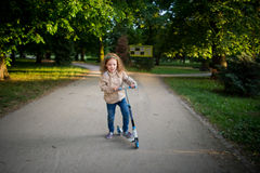 Cute little girl costs with the scooter on a path in city park. Stock Photos