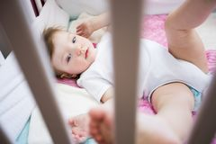 Cute little girl in cradle at baby room Stock Photos
