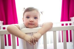 Cute little girl in cradle at baby room Stock Photo