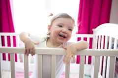Cute little girl in cradle at baby room Stock Image