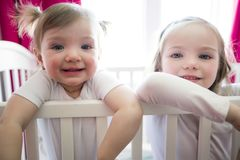 Cute little girl in cradle at baby room with sister Royalty Free Stock Photo